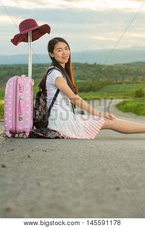 Lonely girl sitting on the road next to her suitcase