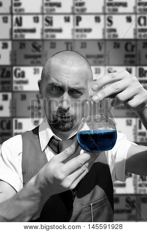 Scientist holding flask with blue liquid on the periodic table of elements background. Science chemistry concept. Black and white photography