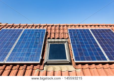 Solar panels and attic window with blue sky