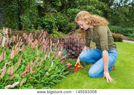 Young caucasian woman works in garden with grass shears