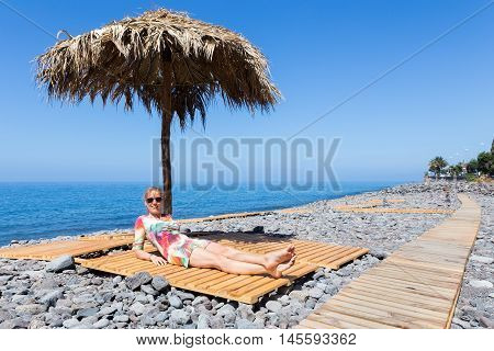 Caucasian middle aged woman sunbathing as tourist on stony beach in Madeira