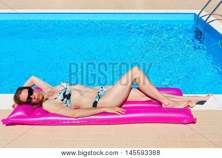 Middle aged woman lying on air mattress at swimming pool