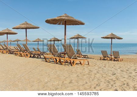 Rows of chairs and umbrellas on the beach of the Mediterranean Sea. Greece. Crete