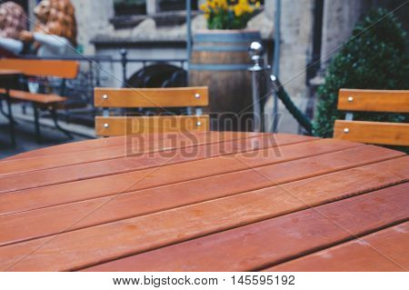 Empty wooden table in street restaurant. Background for product display montage