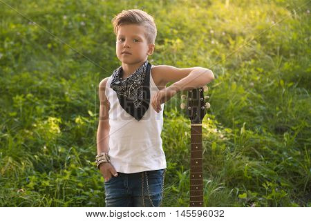 The little boy leaned on the guitar . He is dressed . Standing on the grass . Stylish boy learns to play the guitar