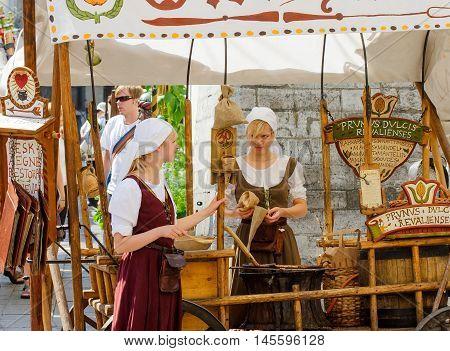 TALLINN, ESTONIA - JULY 8, 2006: Tourists in Old City in Tallinn. Sellers Scandinavian baked breaded almond nuts with cinnamon, garlic, pepper, sugar