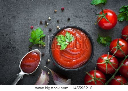 Tomato ketchup sauce  in a bowl with spices, herbs and cherry tomatoes. View from above.