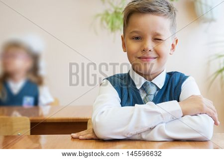 Happy schoolboy sitting at desk, first day in the school
