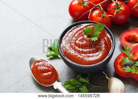 Tomato ketchup sauce  in a bowl with spices, herbs and cherry tomatoes. Selective focus