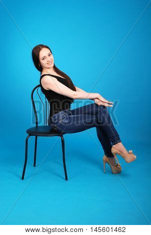 Girl sits sideways on a chair isolated on blue