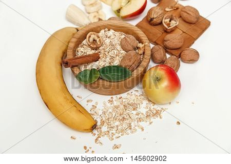 There are Banana,Apple, Walnuts.Wooden Plate and Rolled Oats,Trivet,with Green Leaves,Healthy Fresh Organic Food on the White Background,Top View