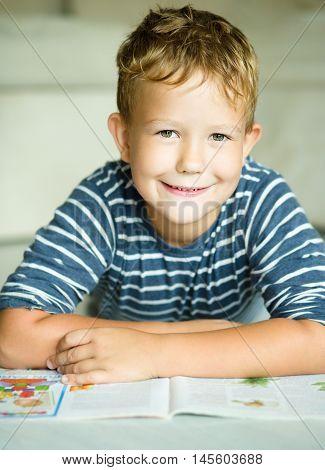 Boy is writing on his copybook in preschool