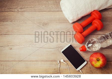 Fitness background with bottle of water dumbbells and smartphone. View from above