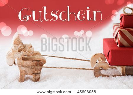 Moose Is Drawing A Sled With Red Gifts Or Presents In Snow. Christmas Card For Seasons Greetings. Red Christmassy Background With Bokeh Effect. German Text Gutschein Means Voucher