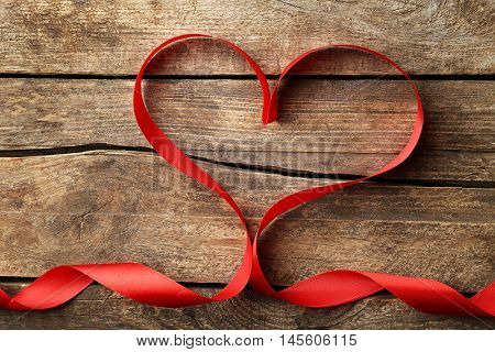 Red ribbon in shape of heart on wooden background, top view