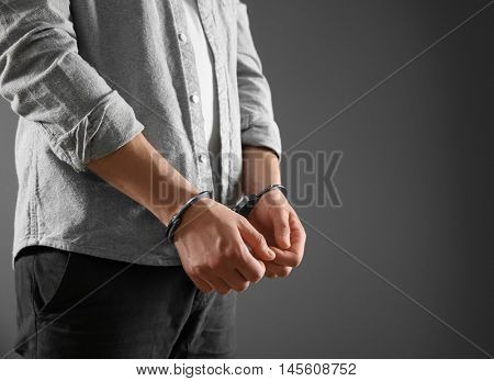 Man in handcuffs on grey background