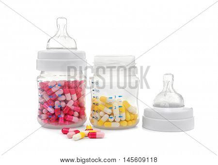 Baby bottles full of colourful pills isolated on white