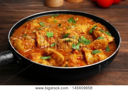 Tasty chicken curry in pan on wooden background