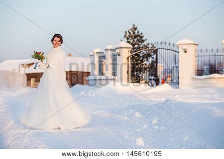 happy and beautiful bride dancing and holds bouquet of orange roses at winter outdoors.