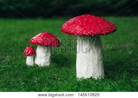 Three amanita muscaria handmade on the grass