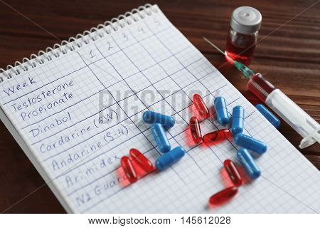 Syringe with pills and notebook. Doping in sport concept