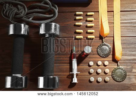 Syringe with dumbbells and pills, top view. Doping in sport concept