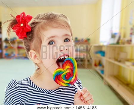 Cute little blonde girl with a red bow on her head, with pleasure licking colorful candy on a stick. Visible language which was painted in a candy color.