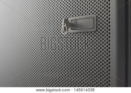 Door metallic black of server rack cabinet. The key is inserted into the door lock. Side lighting and shallow DOF
