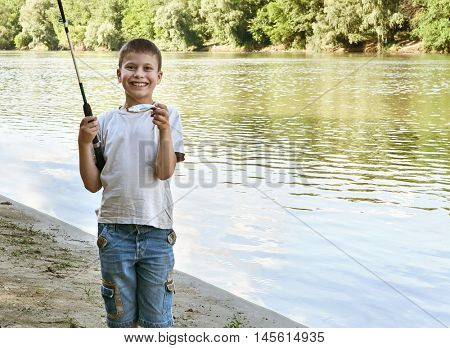 boy catch fish on bait, child camping and fishing, river and forest, summer season