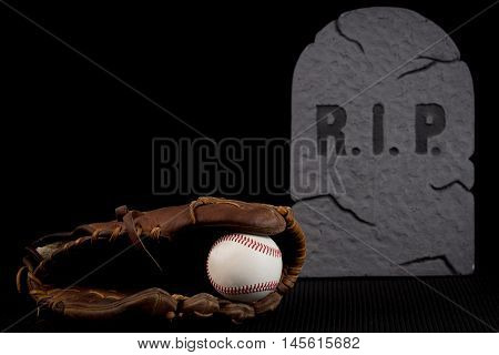 Seasoned leather baseball glove with ball isolated on black background. Bad season or team going through slump.