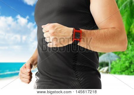 Man with pulsometer on blurred ocean coast background