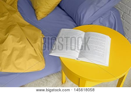 Opened book on yellow bedside table near crumpled bed