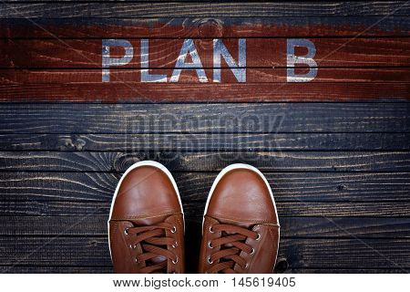 Plan B message and sport shoes on wooden floor