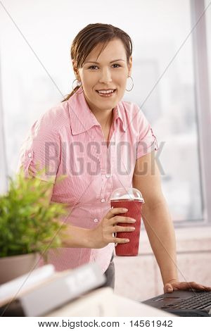 Businesswoman standing at desk holding coffee cup, looking at camera, smiling.?