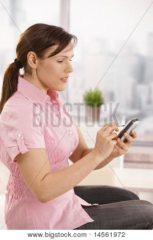 Casual office worker sitting on desk using smartphone, smiling.?