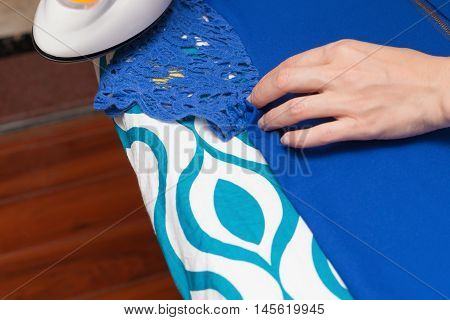 a woman ironing clothes on ironing board
