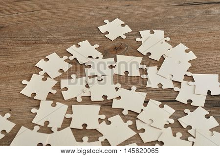 White puzzle pieces on a wooden background