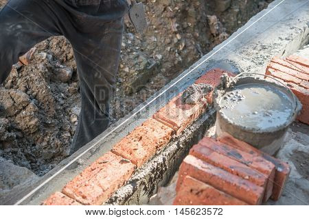 making up a brick wall with cement