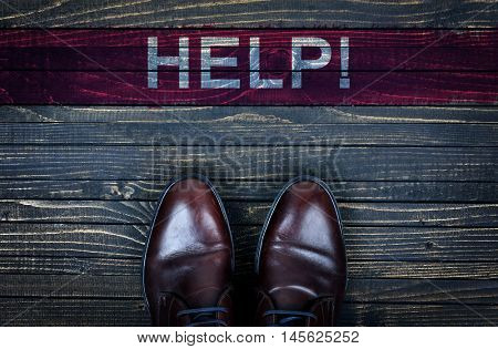 Help message and business shoes on wooden floor