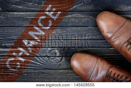 Chance message and business shoes on wooden floor
