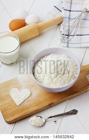 Flour in ceramic bowl with eggs and rolling pin and heart shape on a white wooden background.