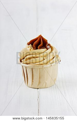 Birthday cupcake on a white wooden surface.
