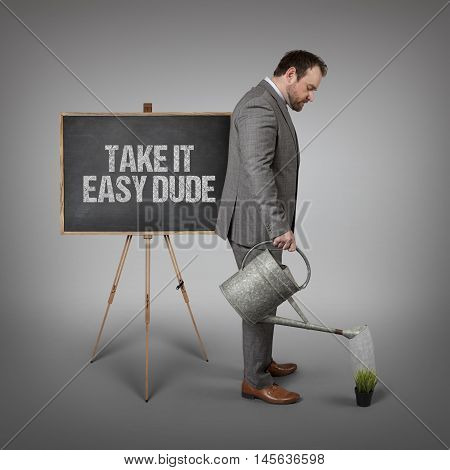 Take it easy dude text on  blackboard with businessman watering plant