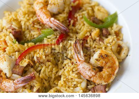 Paella with rice, bell peppers, shrimp in white dish