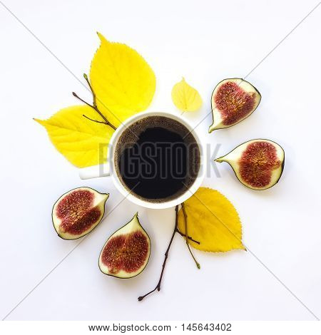 Bright morning cup of coffee with fig fruits. Autumn decoration: yellow leaves and branches. Flat lay top view view from above