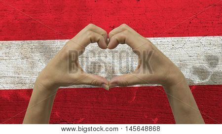 With a stylized Austrian flag background an anonymous person's hands being held in the form of a heart symbolizing love and patriotism for Austria.