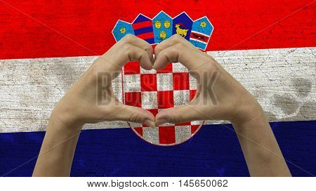With a stylized Croatian flag background an anonymous person's hands being held in the form of a heart symbolizing love and patriotism for Croatia.