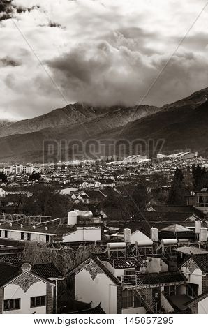 Dali old town rooftop view with cloudy Mt Cangshan. Yunnan, China.
