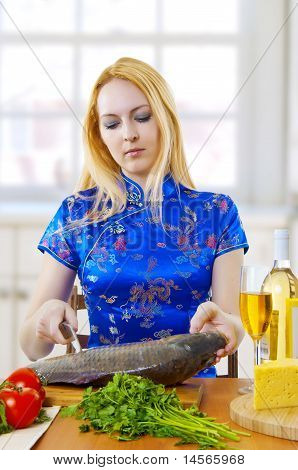 Young Woman Is Cooking Fresh Fish In Kitchen