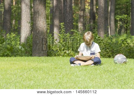 Smart boy using a tablet outdoors. Colored ball near him. Casual clothes. Technology, education, lifestyle, people concept